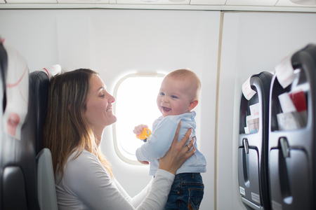 Young mom, playing and breastfeeding her toddler boy on board of aircraft, going on holiday Zdjęcie Seryjne - 99247582