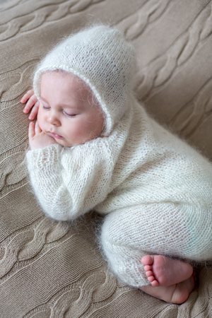 Beatiful baby boy in white knitted cloths and hat, sleeping sweetly posed in bed Imagens