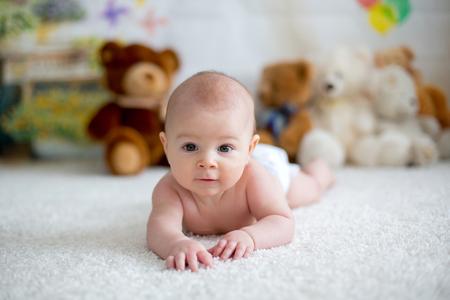 작은 아기 소년 부드러운 곰 장난감 집에서 놀고, 누워 스톡 콘텐츠