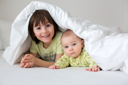 Cute little six month old baby boy and his older brother, playing under duvet at home in bed in bedroom, smiling happily  Stock Photo