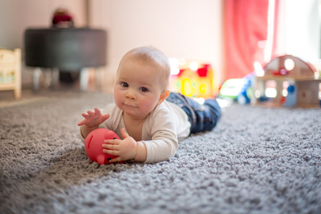 Cute baby toddler boy, playing at home with lots of colorful construction toys Stock fotó