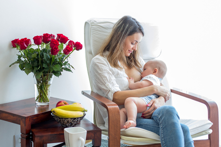 Mother, playing with her toddler boy at home in rocking chair, smiling, breastfeeding Foto de archivo
