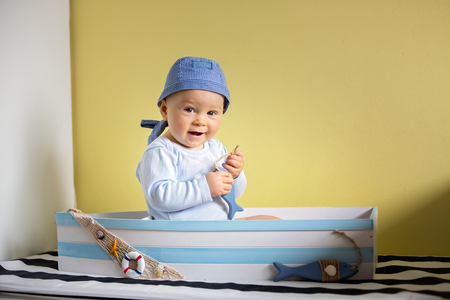 Cute toddler boy, sitting in a big wooden boat at home, playing with wooden fishes, smiling Reklamní fotografie