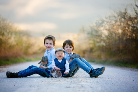 Three children, boy brothers in park, playing with little bunnies on sunset, rural scene Stockfoto