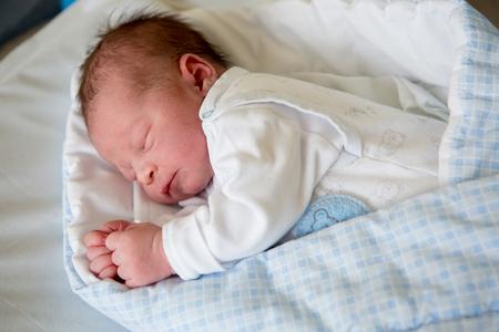 Beautiful newborn baby boy, laying in crib in prenatal hospital