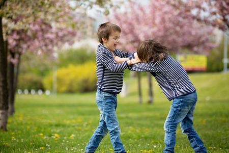 Two children, brothers, fighting in a park, springtime 스톡 콘텐츠