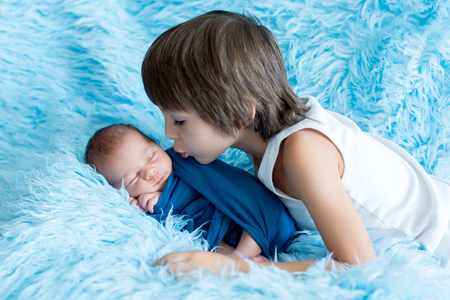 Cute baby boy, peacefully sleeping wrapped in blue wrap, older brother hugging him and giving him a kiss