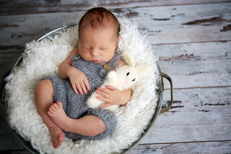 Newborn baby boy, sleeping peacefully in basket, dressed in knitted outfit, chilling out, happy and cute Stock Photo