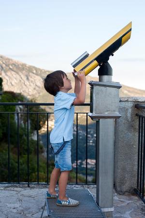 Niño curioso, mirando a través de un telescopio algo interesante, verano