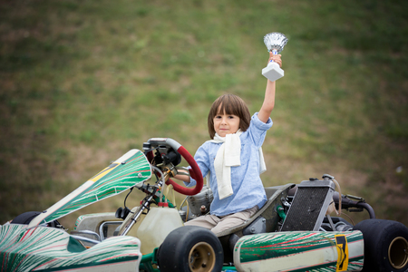 Cute child, riding go cart, wins champion cup, happiness winner concept