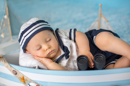 Cute toddler baby boy sleeping in wooden boat with fishes, starfish and binoculars, dressed as sailman, indoors shot