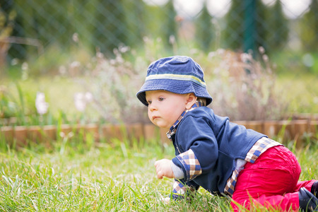 Sweet toddler boy in garden, child playing with little bunny, springtime, outdoors