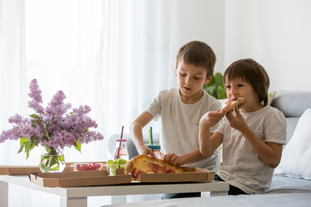 Beautiful young family with children, eating pizza at home and watching TV on a sunday