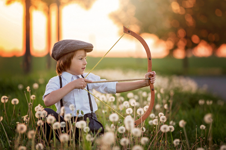 Portrait of child playing with bow and arrows, archery shoots a bow at the target on sunset Stockfoto - 101729027