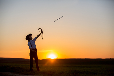 Silhouette of child playing with bow and arrows, archery shoots a bow at the target on sunset Stock fotó - 101729017