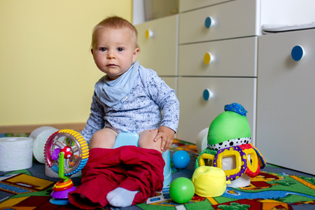 Smiling baby sitting on chamber pot with lots of toys and toilet paper around him in kids room