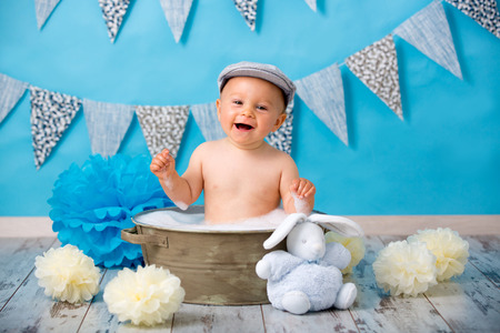 Cute baby boy, having bath after smash cake, isolated shot on blue background