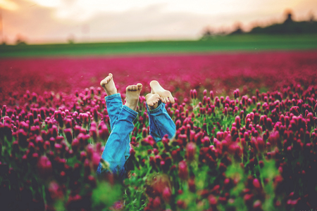 Beautiful children in gorgeous crimson clover field on sunset, springtime. Kids feet seen over the flowers