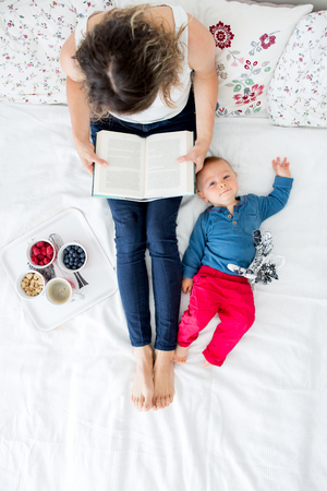 Mother and toddler baby boy, lying in bed, baby playing, mom reading a book and eating fruits, high angle shot, from above. Happy family concept 免版税图像