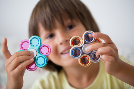 Young boy play with fidget spinner stress relieving toy at home  Reklamní fotografie