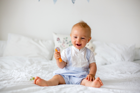 Happy baby eating carrot. Healthy nutrition for kids. Bio carrot as first solid food for infant. Toddler eat vegetables