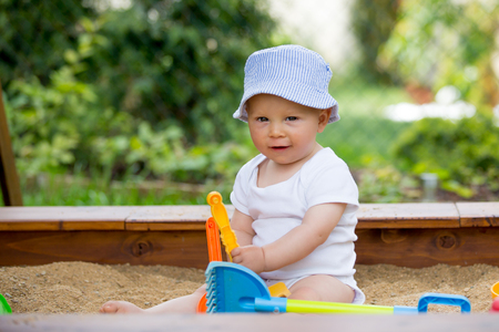 Little baby boy, playing in a sandpit with toys outdoors