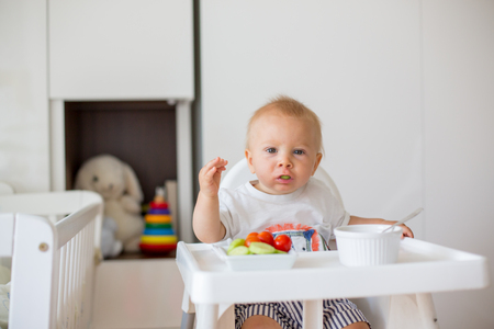 Sweet baby child, boy, eating mashed food and fresh vegetables, sitting in high baby chair in kids room Stock Photo