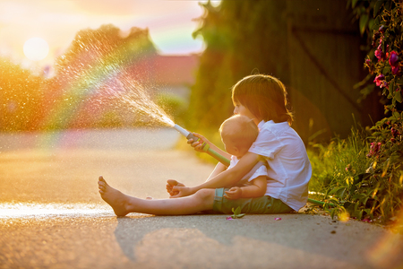 Adorable little children, brothers, playing together with a garden hose on hot and sunny summer day on sunset, siblings having fun outdoors Banco de Imagens