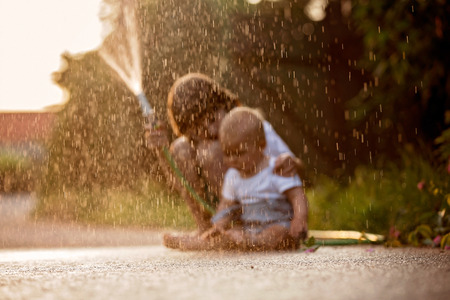 Adorable little children, brothers, playing together with a garden hose on hot and sunny summer day on sunset, siblings having fun outdoors Stock Photo