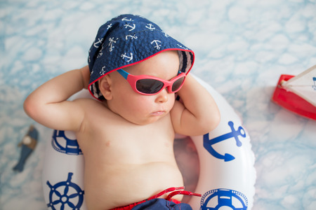 Cute toddler, baby boy sleeping on a tiny inflatable swim ring,  wearing swimsuit shorts and sunglasses, indoor shot Stock Photo