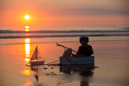 Cute baby child, sweet boy, playing with boat, teddy bear and fishes on sunset at the edge of the ocean, beautiful sunset, reflection Stock Photo