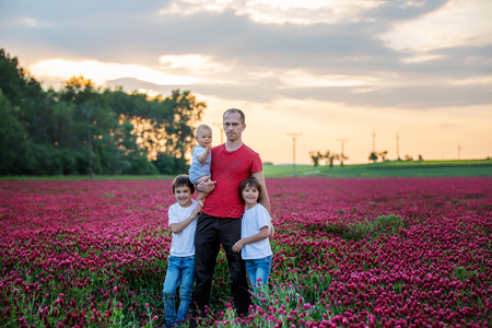Father, having his portrait with his three sons, boys, in crimson clover field on sunset, springtime