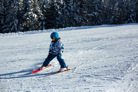 Cute preschool child, skiing in Austrian winter resort on a clear day, wintertime