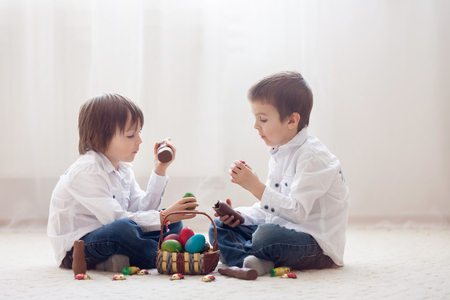 Two adorable little children, boy brothers, having fun eating chocolate bunnies and playing with eggs at home, back light Stok Fotoğraf