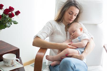 Mutter, spielt mit ihrem Kleinkind zu Hause im Schaukelstuhl, lächelt, stillt Standard-Bild - 107469882
