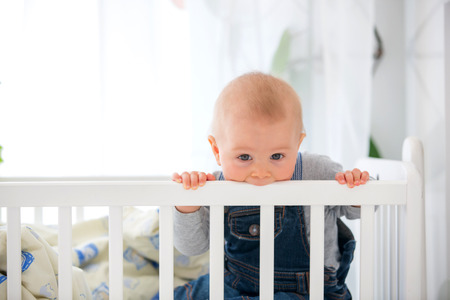 Little toddler boy, crying in crib after waking up, toys in bed
