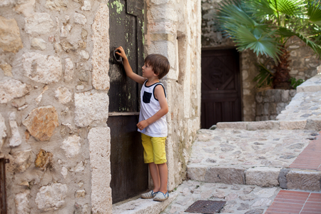Little boy, knocking on a old medieval door in an old village