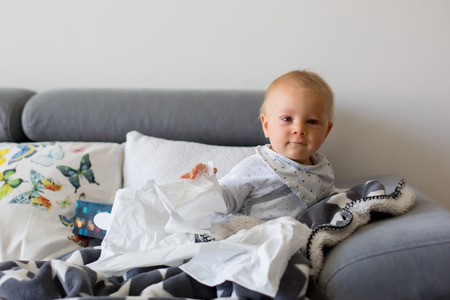 Sick little toddler boy, sitting on a couch in living room with a box of tissues Stock Photo