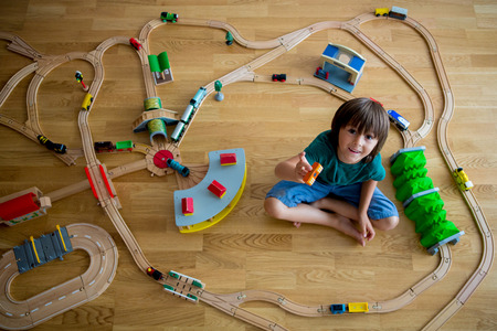 Sweet preschool child, boy, playing with wooden railway and trains at home, top view Stock fotó