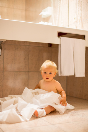 Toddler baby boy, child ripping up with toilet paper in bathroom 写真素材 - 107472178