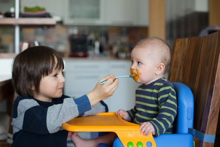 Cute preschool boy, feeding his baby brother with mashed vegetables, baby eating mashed food for the first time 스톡 콘텐츠