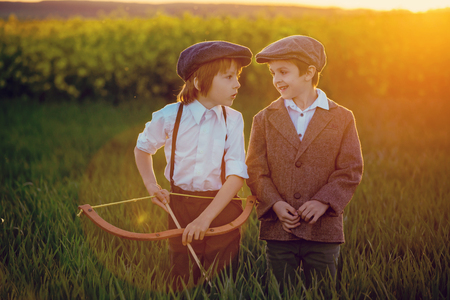 Portrait of children playing with bow and arrows, archery shoots a bow at the target on sunset Stock Photo