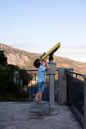 Curious boy, looking through a telescope at something interesting, summertime Stock fotó