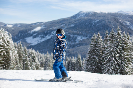 Cute preschool child, skiing in Austrian winter resort on a clear day, wintertime