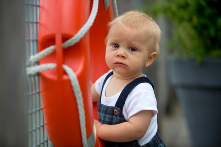 Sweet toddler baby boy, playing with plastic orange saving belt by the railing fence of the ferry Stock Photo