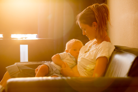 Young mother, breastfeeding on sunset on quiet evening her little baby boy in sunny living room