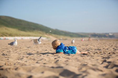 Cute baby boy, adorable child, playing with seagulls at the edge of the ocean coast Stock Photo - 107472711