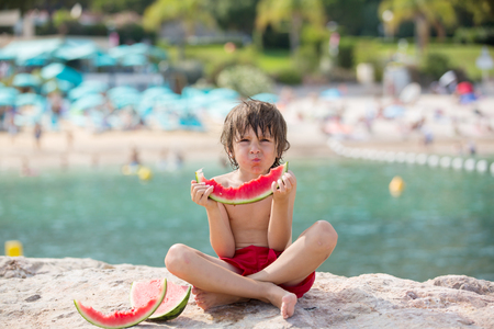 Cute little child, boy, eating watermelon on the beach, summertime