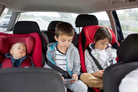 Three children, boys, siblings, traveling in car seats, going on holday