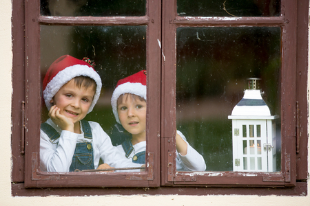 Two cute boys, brothers, looking through a window, waiting impatiently for Santa Archivio Fotografico - 107472757